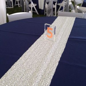 white sequin table runner and acrylic table number
